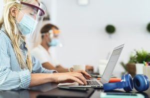 woman using laptop wearing covid surgical mask